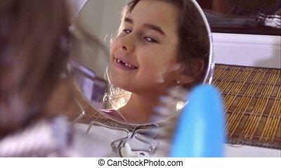 teen girl combing her hair before a mirror indoor