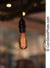 Ornamental light bulb lit up and hanging from the ceiling...