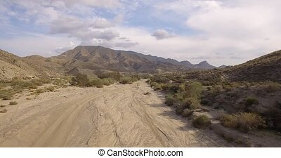 Aerial, Flight over a dry riverbed - Shot is straight out of...