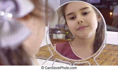 teen girl combing indoor her hair before mirror
