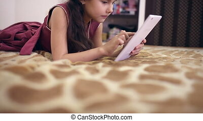 teen girl with tablet on bed playing online internet - teen...