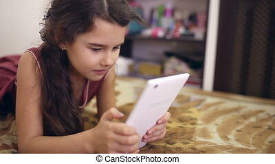girl teen with tablet on bed playing internet online - girl...