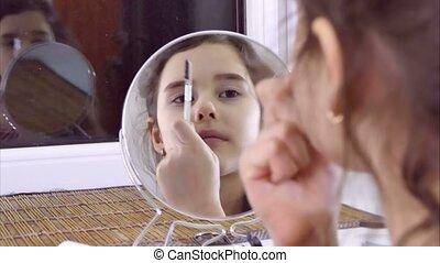 teen girl doing makeup eyebrow comb indoor - teen girl doing...