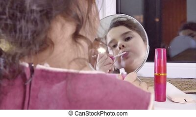 girl teen paints lips before indoor mirror - girl teen...