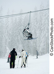 skilift - vertical photo of skiing people, ski-lift detail