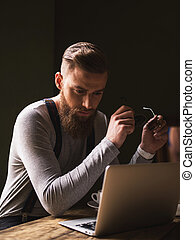 Cheerful bearded guy is working with a laptop - Handsome...