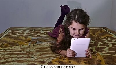teen girl playing tablet on bed - teen girl playing tablet...