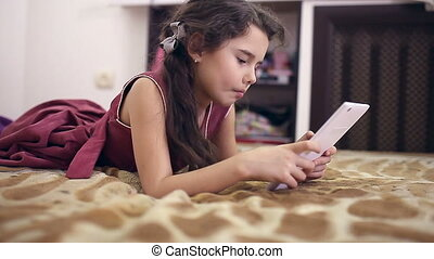 teen girl daughter with tablet on bed playing internet...
