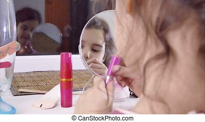 girl teen paints lips before mirror indoor - girl teen...