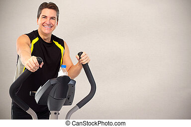 Man exercising on elliptical trainer Dieting and sport...