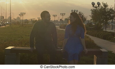 Man and woman talking sitting on bench during sunset.