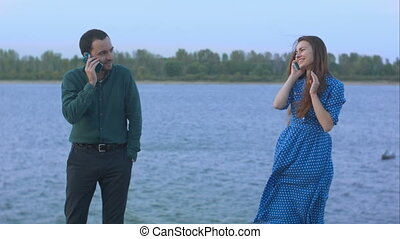 Man and woman with cell phones talking.
