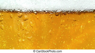 bubbles movement inside a glass of beer with drops and foam...