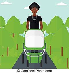 Woman pushing pram. - An african-american mother walking...