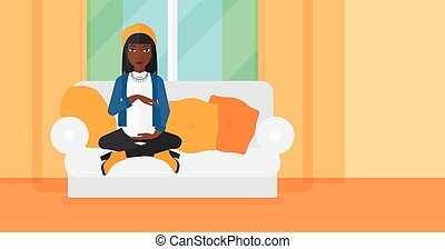Pregnant woman sitting on sofa - An african-american...