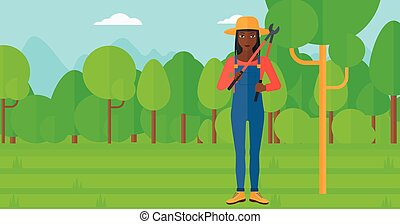 Farmer with pruner in garden - An african-american woman...