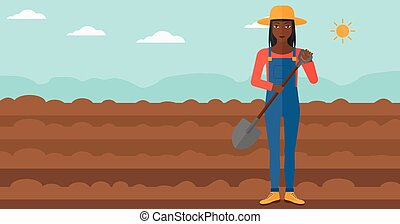 Farmer on the field with shovel. - An african-american woman...