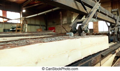 Woodworking. Processing of sawn logs on machine, close-up
