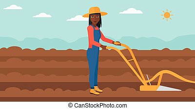 Farmer on the field with plough. - An african-american woman...