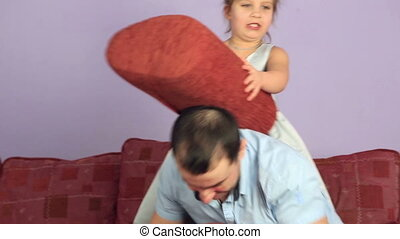 Cheerful father and daughter fighting pillows on couch.