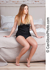 Young attractive woman in sexy bodysuit sitting on the bed