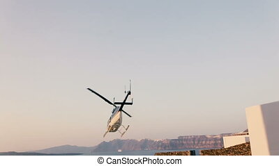 Helicopter flying on blue sky with mountains on the background