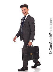 laughing young businessman is walking with suitcase