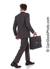 back view of a walking businessman with briefcase looking to...