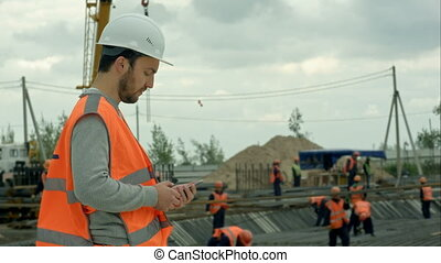Construction worker talking on the phone at a building site....