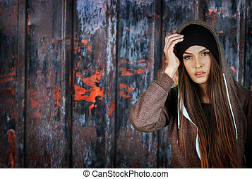 Teenager girl hipster on rusty fence background. Wearing...