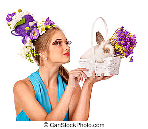 Woman in easter style holding eggs and flowers.