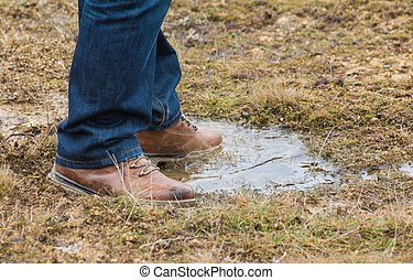 Feet of a person standing in a puddle of water - Feet of a...