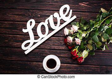 Inscription love and roses on wood background
