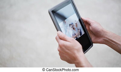 happy couple with tablet pc viewing photos at home - love,...
