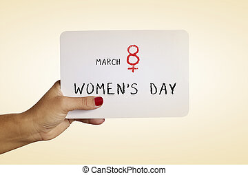 text march 8 womens day in a signboard - the hand of a young...