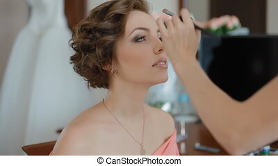 Makeup artist doing visage to young woman indoor Doing nose...