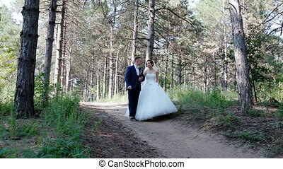 Bride and groom walk in the pine wood They look at each...