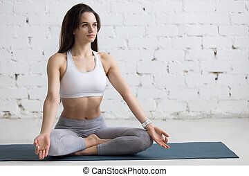Yoga Indoors: Sukhasana pose - Beautiful young woman working...