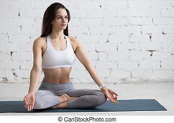 Yoga Indoors: Sukhasana pose - Beautiful young woman working...