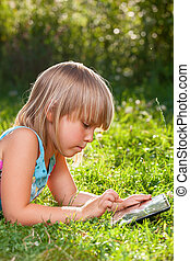 Child using a tablet computer outdoor - Little girl usng a...