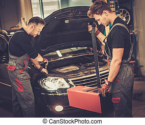 Professional car mechanics inspecting headlight lamp of automobile in auto repair service.