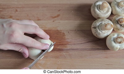 Woman's hands cutting mushroom champignon