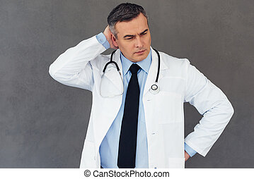 Hard to diagnose. Mature male doctor scratching his head and looking away while standing against grey background