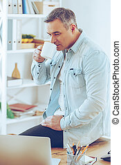 Coffee break. Mature man drinking coffee and looking at his laptop while leaning at the desk in office