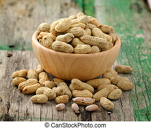 peanuts in a wood bowl on a wooden table