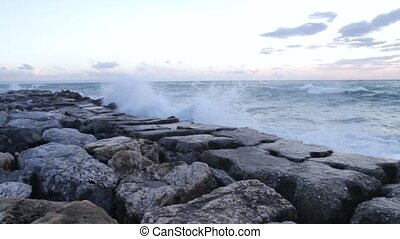 Waves crashing on the breakwater with rough sea and dark sky