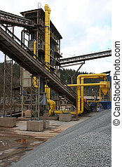 Stone quarry with silos, conveyor belts and piles of stones....