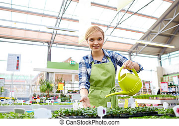 happy woman with watering can in greenhouse - people,...