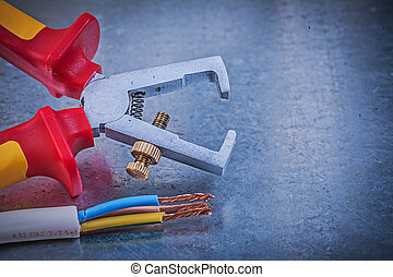 Insulated strippers electrical wires on metallic background...
