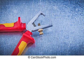 Insulated wire strippers on metallic background electricity...